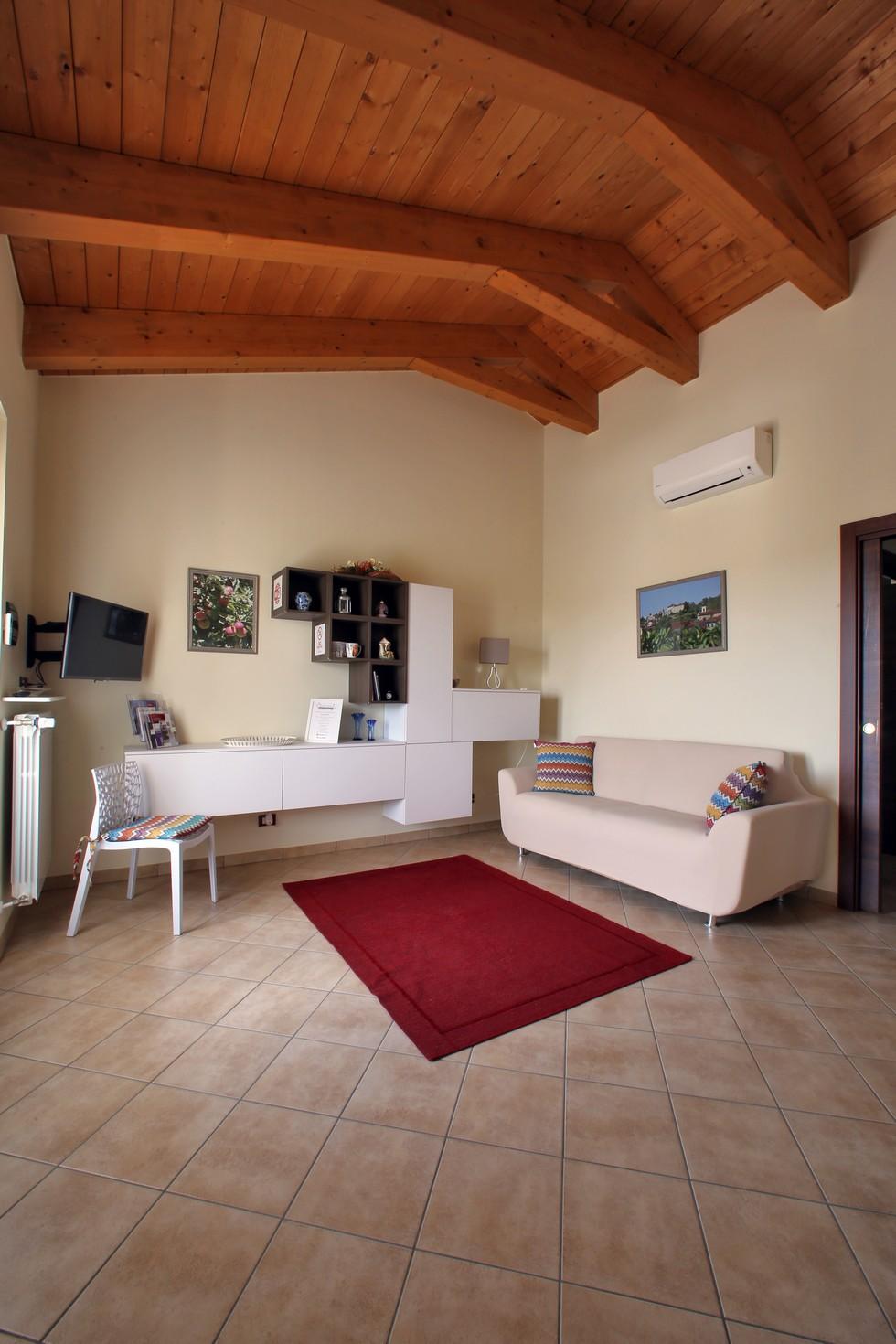 Salotto moderno con divano sedia, scrivania, scaffali